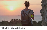 Купить «Female traveler with backpack taking photo of sunset sea on her phone», видеоролик № 32285980, снято 14 июня 2017 г. (c) Vasily Alexandrovich Gronskiy / Фотобанк Лори