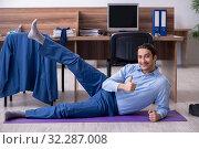 Купить «Young handsome businessman doing exercises at workplace», фото № 32287008, снято 8 мая 2019 г. (c) Elnur / Фотобанк Лори