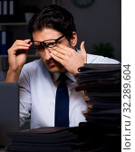 Купить «Young businessman working overtime late in office», фото № 32289604, снято 4 октября 2017 г. (c) Elnur / Фотобанк Лори