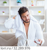 Купить «Young man in a bathrobe watching television at home on a sofa co», фото № 32289976, снято 7 июля 2017 г. (c) Elnur / Фотобанк Лори