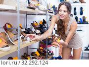 Cheerful woman choosing pair of summer shoes. Стоковое фото, фотограф Яков Филимонов / Фотобанк Лори