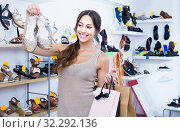 portrait of woman with shopping bags having picked shoes in hands in shop. Стоковое фото, фотограф Яков Филимонов / Фотобанк Лори