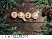 Купить «New Year composition, 2020 simbols and fir branches with cones on old wooden background», фото № 32295040, снято 13 октября 2019 г. (c) Майя Крученкова / Фотобанк Лори