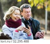 Купить «Couple with mobile phones», фото № 32295488, снято 17 октября 2019 г. (c) Яков Филимонов / Фотобанк Лори