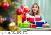 Купить «Portrait of happy girl with X-mas presents at home», фото № 32295572, снято 11 декабря 2019 г. (c) Яков Филимонов / Фотобанк Лори