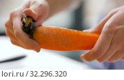 Купить «hands peeling carrot with vegetable peeler», видеоролик № 32296320, снято 10 октября 2019 г. (c) Syda Productions / Фотобанк Лори