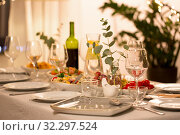 Купить «table served with plates, wine glasses and food», фото № 32297524, снято 15 декабря 2018 г. (c) Syda Productions / Фотобанк Лори
