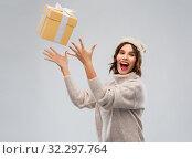 Купить «young woman in winter hat catching gift box», фото № 32297764, снято 30 сентября 2019 г. (c) Syda Productions / Фотобанк Лори
