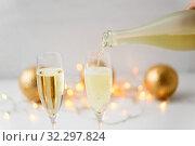 Купить «champagne pouring from bottle to christmas glasses», фото № 32297824, снято 26 сентября 2018 г. (c) Syda Productions / Фотобанк Лори