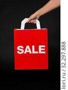 Купить «hand holding red shopping bag with sale word», фото № 32297888, снято 20 декабря 2018 г. (c) Syda Productions / Фотобанк Лори