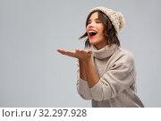 Купить «young woman in knitted winter hat sending air kiss», фото № 32297928, снято 30 сентября 2019 г. (c) Syda Productions / Фотобанк Лори