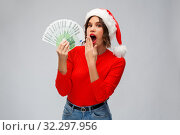 Купить «surprised woman in santa hat with money», фото № 32297956, снято 30 сентября 2019 г. (c) Syda Productions / Фотобанк Лори
