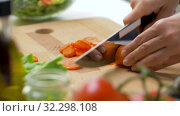 Купить «woman chopping carrot with kitchen knife at home», видеоролик № 32298108, снято 10 октября 2019 г. (c) Syda Productions / Фотобанк Лори