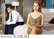 Купить «Upset woman with phone and with frustrated man», фото № 32298264, снято 24 сентября 2018 г. (c) Яков Филимонов / Фотобанк Лори