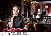 Young woman holding glass of white wine in luxurious restaurant. Стоковое фото, фотограф Яков Филимонов / Фотобанк Лори