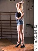 Купить «Young woman in denim shorts practicing pole dancing», фото № 32298524, снято 7 декабря 2019 г. (c) Яков Филимонов / Фотобанк Лори