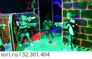Modern preteen girls and boys of different nationalities with laser pistols playing laser tag on dark labyrinth. Стоковое видео, видеограф Яков Филимонов / Фотобанк Лори