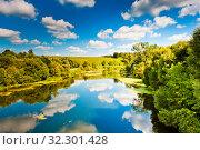 Купить «Небо с белыми большими облаками отражается в воде. Красивый подмосковный пейза. Летний солнечный день», фото № 32301428, снято 20 августа 2019 г. (c) E. O. / Фотобанк Лори