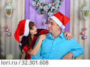 A guy and a girl in Christmas hats look at each other. Стоковое фото, фотограф Арестов Андрей Павлович / Фотобанк Лори