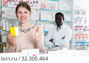 Купить «Satisfied woman with medicines showing thumb up», фото № 32305464, снято 2 марта 2018 г. (c) Яков Филимонов / Фотобанк Лори