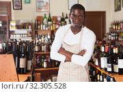 Купить «Salesman of wine shop standing near shelves», фото № 32305528, снято 1 августа 2019 г. (c) Яков Филимонов / Фотобанк Лори