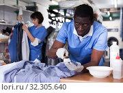 Купить «Laundry worker during daily work», фото № 32305640, снято 15 января 2019 г. (c) Яков Филимонов / Фотобанк Лори