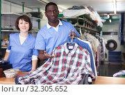 Купить «Workers of laundry showing clean clothing», фото № 32305652, снято 15 января 2019 г. (c) Яков Филимонов / Фотобанк Лори