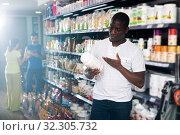 Купить «Athletic African looking for necessary food supplements», фото № 32305732, снято 18 февраля 2020 г. (c) Яков Филимонов / Фотобанк Лори