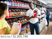 Купить «focused muscular African man choosing sports nutrition products in shop, reading content label», фото № 32305740, снято 8 декабря 2019 г. (c) Яков Филимонов / Фотобанк Лори