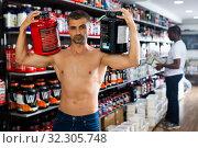Купить «sportsman with cans of sports nutrition», фото № 32305748, снято 14 ноября 2019 г. (c) Яков Филимонов / Фотобанк Лори