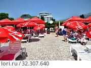 Купить «Budva, Montenegro - June 13.2019. City beach in the resort area with red umbrellas with Coca Cola brand», фото № 32307640, снято 13 июня 2019 г. (c) Володина Ольга / Фотобанк Лори