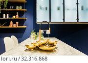 Современный интерьер кухни с белой мраморной столешницей на фоне синей стены. Стоковое фото, фотограф Светлана Васильева / Фотобанк Лори