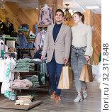 Купить «Smiling couple is satisfied of purchases and walking with package», фото № 32317848, снято 12 марта 2018 г. (c) Яков Филимонов / Фотобанк Лори