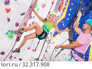 Купить «Instructor giving instructions to woman on wall climbing», фото № 32317908, снято 9 декабря 2019 г. (c) Яков Филимонов / Фотобанк Лори