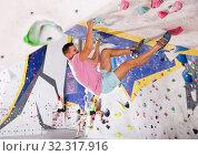 Купить «Male alpinist practicing indoor rock-climbing on artificial boulder without safety belts», фото № 32317916, снято 13 ноября 2019 г. (c) Яков Филимонов / Фотобанк Лори