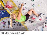 Купить «Female practicing indoor rock-climbing», фото № 32317924, снято 9 июля 2018 г. (c) Яков Филимонов / Фотобанк Лори