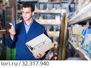 Купить «Foreman is choosing small details in building shop», фото № 32317940, снято 26 июля 2017 г. (c) Яков Филимонов / Фотобанк Лори