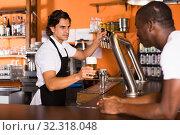 Купить «Young man barman giving beer with foam to man client», фото № 32318048, снято 28 августа 2019 г. (c) Яков Филимонов / Фотобанк Лори