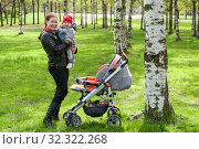 Купить «Mother holding toddler child on arms, standing next to stroller in summer rark with birches tree and green grass», фото № 32322268, снято 16 мая 2009 г. (c) Кекяляйнен Андрей / Фотобанк Лори