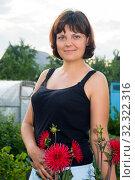Portrait of Caucasian smiling woman with red flowers, dresed black singlet, standing outdoor. Стоковое фото, фотограф Кекяляйнен Андрей / Фотобанк Лори