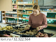 Woman choosing potatoes in grocery store. Стоковое фото, фотограф Яков Филимонов / Фотобанк Лори