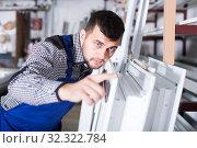 Купить «Handsome workman inspecting PVC manufacturing», фото № 32322784, снято 30 марта 2017 г. (c) Яков Филимонов / Фотобанк Лори