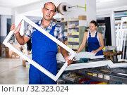 Купить «Positive foreman in blue overalls fun demonstrating window frame in factory», фото № 32323024, снято 19 июля 2017 г. (c) Яков Филимонов / Фотобанк Лори