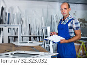 Купить «Focused workman in overalls controlling quality of assembly of plastic window in workshop», фото № 32323032, снято 19 июля 2017 г. (c) Яков Филимонов / Фотобанк Лори