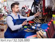 Купить «Adult male is making rediscount of new instruments in tools store.», фото № 32326880, снято 9 января 2018 г. (c) Яков Филимонов / Фотобанк Лори