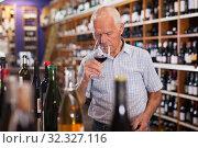 Купить «Man tasting wine in wine store», фото № 32327116, снято 8 мая 2019 г. (c) Яков Филимонов / Фотобанк Лори