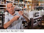Купить «Man tasting wine in wine store», фото № 32327132, снято 8 мая 2019 г. (c) Яков Филимонов / Фотобанк Лори