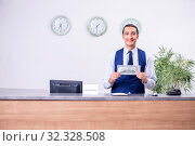Young man receptionist at the hotel counter. Стоковое фото, фотограф Elnur / Фотобанк Лори