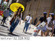 A woman channels the 1960Õs as she walks on Seventh Avenue in New York on Tuesday, August 20, 2019. Редакционное фото, фотограф Richard Levine / age Fotostock / Фотобанк Лори