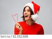 Купить «happy young woman in santa hat on christmas», фото № 32332608, снято 30 сентября 2019 г. (c) Syda Productions / Фотобанк Лори